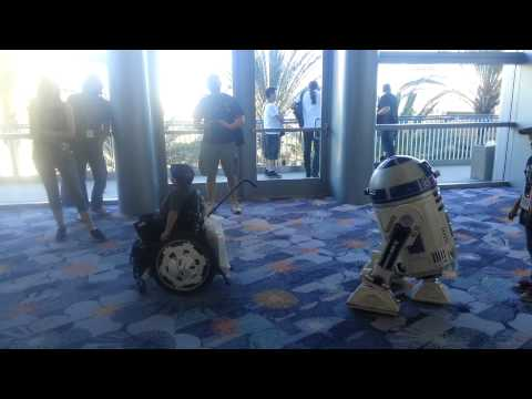 At Star Wars Celebration a child in a wheelchair plays with a fan made R2-D2 unit.