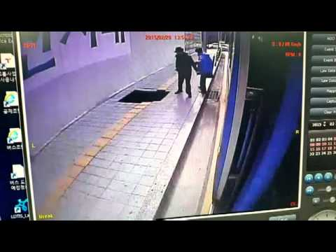 Two people fall into a hole that has suddenly opened on the pavement in South Korea.