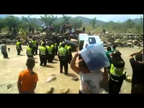 Colombianos cantan el Himno Nacional mientras cruzan el rió Tachira en Venezuela