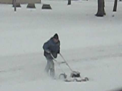 Man uses push lawn mower to blow snow.