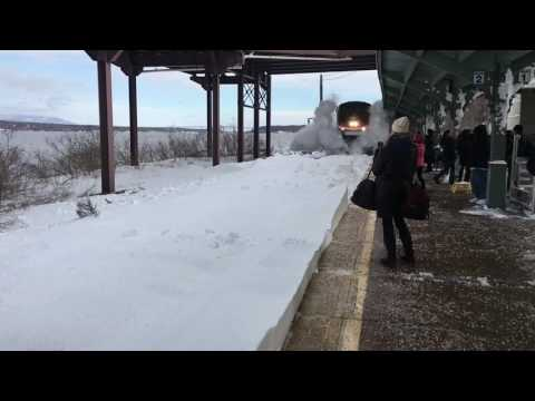 A Moving Train Showers Waiting Passengers With Snow As It Moves Into the