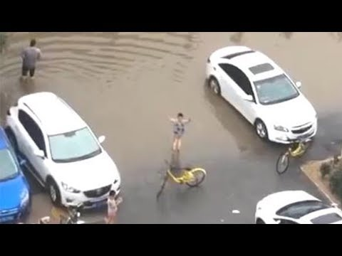 Boy steers traffic away from flooded road in Hebei Province
