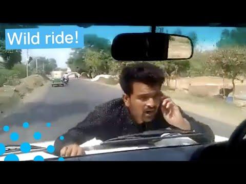 Sisukas mielenosoittaja saa kyydin auton konepellillä