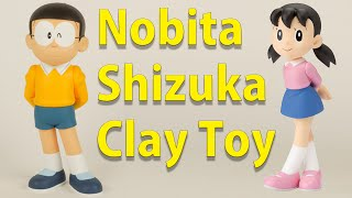 Play With Clay Japanese - How To Make Nobita & Shizuka - Claytohe. Nobita wears glasses, a red or yellow polo shirt with a white collar, and blue or black sh...