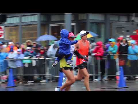 Man carries child across Boston Marathon finish line