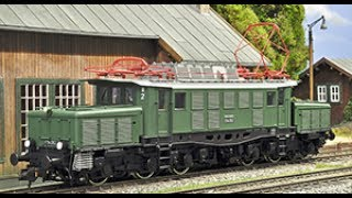 """REYNAULDS.COM presents a video on the new ESU HO Scale German electric locomotive class E94, also known as the German """"Crocodile"""". The E94 was truly a unique locomotive due to their articulated three-part frame. The Deutsche Reichsbahn had the mighty E94's developed as a more powerful successor to the class E93. Delivery of the first locomotives commenced in 1940 during World War II. Since the class E94 was important for the war effort they were not subject to delivery stops due to shortages of raw materials. A total of 146 locomotives were built between 1940 and 1945.  The E94 was a very impressive and powerful locomotive, it's output was 3300kW and a had a top speed of 90 km/h. In 1946 the newly commissioned Deutsche Bundesbahn(German Federal Railways)put another 49 locomotives into service which ran until 1956. After 1956 the Deutsche Bundesbahn was in need of stronger locomotives to deal with increasing freight demands so the power output of the last remaining 23 locomotives had been increased to 4680kW with a top speed of 100km/h. Due to considerable technical differences they were re-classified to E94.2 (later on this was changed to class 194.5). After the war 44 locomotives remained in Austria and were renamed as class 1020. Most of the Austrian units experienced considerable modifications during the 1960's. The E94's that had been located within the Soviet occupied zone were transferred to the Soviet Union and returned to the DR (Deutsche Reichsbahn, German Democratic Republic) in 1952. The DR arranged for the refurbishment of 23 units, which were mainly hauling heavy freight trains and occasionally heavy express trains. In the west the DB also used the E94's in heavy freight service; however once in awhile they were also used for hauling commuter trains, which, occasionally, only consisted of two pairs of """"Umbauwagen"""" (rebuilt coaches) and thus the locomotive was heavier than the train. In 1985 the DB decommissioned the last """"German Crocodiles"""" while the DR"""