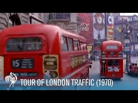 1970 - London. A sightseeing tour by car - travelling shots of London streets. Various scenes showing London taxis (black cabs) and double decker buses weaving thei...