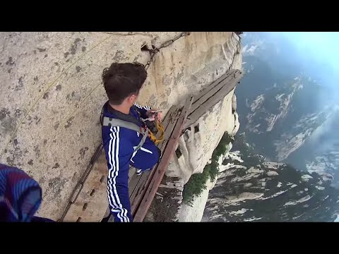 Guy removes harness to walk on a narrow plank in the