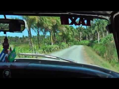 A ride in an old American taxi through the village Baracoa in Cuba