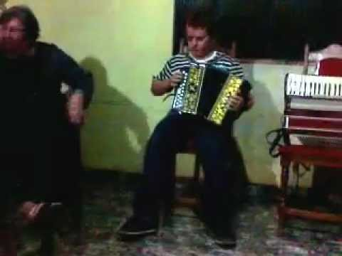 o menino do altisimo tocando gaita entre amigos em itaipulandia p .r brasil