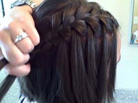 Hairdresser creating waterfall braids on woman