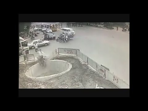 Fail - A man in China crashes his scooter multiple times before driving and falling into a hole. Luckily he wasn't seriously injured.