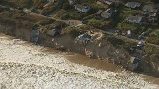 Worst tidal surge in 60 years batters UK east coast and drags homes into the sea