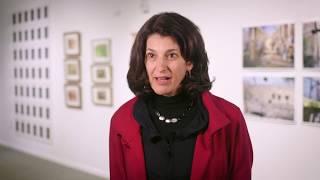 Jody Biehl sits in art gallery describing her exhibit on refugees in Buffalo.