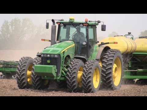 illinois - A 24 row John Deere planter pulled by a John Deere tractor puts down seed corn in a triangular-shaped field in DeKalb County, Illinois. The field was being p...