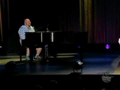 Guy laughing while insulted at a comedy show, but plays the piano beautifully
