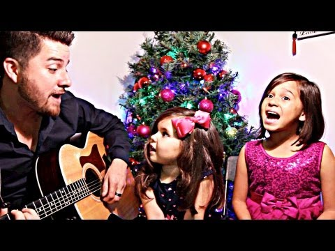 "Father sings ""Jingle Bells"" with his two daughters."