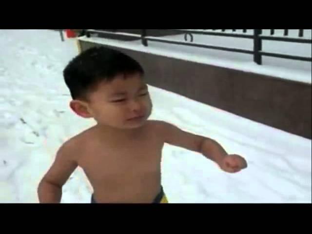 Em bé cởi trần chạy dưới trời tuyết