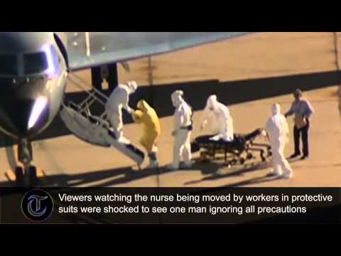 wearing - Viewers watching a nurse infected with Ebola being helped onto a plane by workers in protective suits were shocked to see one man ignoring all precautions. TV cameras filmed from afar as US...