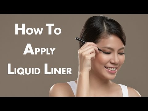 Applying liquid eyeliner to the top lid