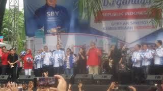 """BOGOR, KOMPAS.com - Ketua Umum Partai Demokrat Susilo Bambang Yudhoyono atau SBY sempat menghibur warga Cikeas saat menghadiri HUT RI ke-72 Fraksi Partai demokrat DPR RI di lapangan Puri Cikeas, Desa Nagrag, Bogor, Jawa Barat, Kamis (17/8/2017).SBY bersama musisi Kikan dan Candil tampil di atas panggung menyanyikan lagu """"Rumah Kita.""""Sang istri yang ikut mendampingi, Ani Yudhoyono, pun nampak sesekali ikut bernyanyi.""""Untuk rumah kecil kita yang kita cintai, Cikeas, dan rumah besar yang kita banggakan, Indonesia,"""" ujar SBY sebelum mulai bernyanyi.Warga pun membalas dengan bertepuk tangan dan lambaian.SBY tampak santai mengenakan kemeja berwarna merah terang dan dipadu dengan celana coklat muda. Sementara sang istri, Ani Yudhoyono, memakai kemeja kotak-kotak dirangkap dengan rompi berwarna biru. Penampilan SBY berbeda dengan sejumlah petinggi Partai Demokrat yang mengenakan seragam berwarna biru. Begitu juga dengan putra keduanya yang menjabat sebagai ketua fraksi Partai Demokrat, Edhie Baskoro Yudhoyono atau akrab disapa IbasSelain upacara, Partai Demokrat juga menggelar bazaar makanan dan berbagai macam perlombaan. SBY didampingi Ani Yudhoyono dan Ibas pun sempat menyaksikan final lomba Voli.Presiden keenam RI itu tiba sekitar pukul 14.30 WIB. Sedangkan Ibas datang lima belas menit lebih awal.Sebelumnya SBY menghadiri upacara peringatan kemerdekaan ke-72 RI di Istana Presiden, Kamis (17/8/2017) pagi.Untuk  pertama kali setelah lengser  dari kursi presiden  keenam RI, SBY menghadiri upacara detik-detik proklamasi di Istana.Sejak Joko Widodo menjabat sebagai Presiden, SBY tidak pernah hadir di istana saat peringatan kemerdekaan."""