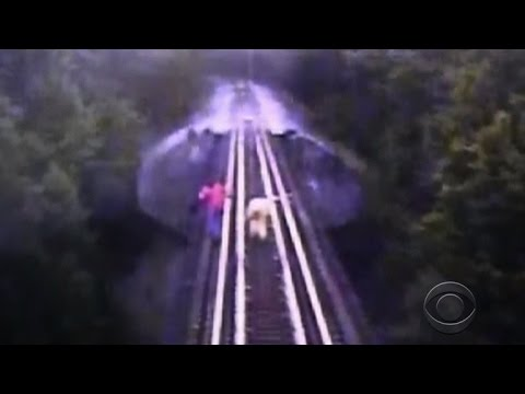 this morning - A camera mounted on a train engine captured the dramatic escape of two women who were caught on the tracks of a railway bridge. The women made a split-second decision to dive between the tracks...