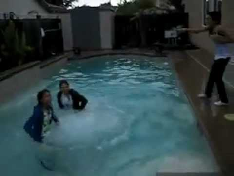 Teenage girls pushing each other into pool