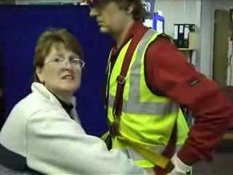 mannequin-man performming as a Living Mannequin: Fall arrest harness being put onto mannequin man by member of the public at a Safety clothing and PPE exhibition by ARCO at family open day at BAE (British Aerospace Engineering) systems in Rochester #5 (flash) for Arco on 06/07/2002