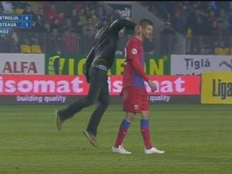 Violent - Violent scenes at a Romanian football match between Steaua Bucharest & Petrolul Ploiesti as a fan runs on the pitch & punches defender George Galamaz. Report...