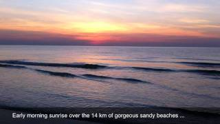 High def video showing the sun coming up over the beach and resort.