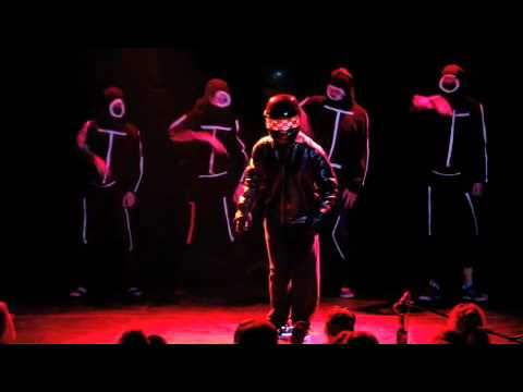 A frame from the video showing the helmeted protagonist and backup dancers