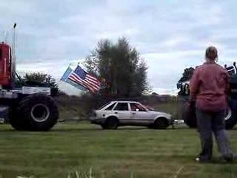 Two monster trucks pull apart a car in epic tug-of-war battle