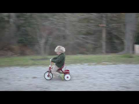 Father Pushes Son On Tricycle With A Leafblower