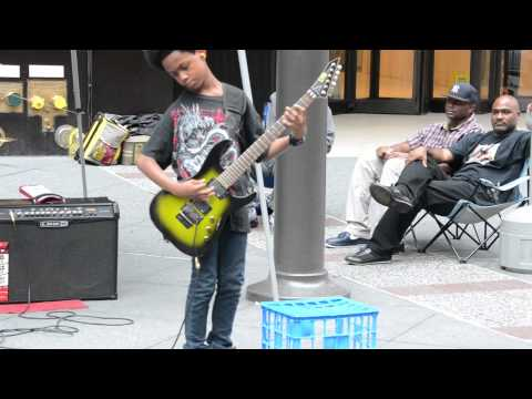 heavymetal - This amazing Black Kid playing heavy metal music on a New York City street corner with his parent present.