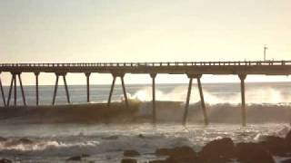 Surfer takes off and shoots through the pillings of the pier
