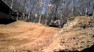 10. John Deere gator 825i pulling a bobcat uphill.
