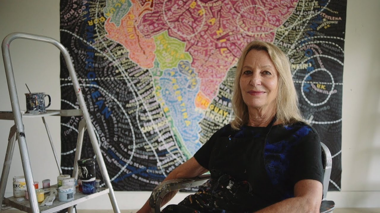 Paula Scher in her studio with a painting behind her