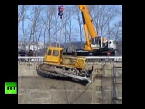 Bulldozer und ein 25t schwerer Kran stürzen in eine Baustellengrube in Russland