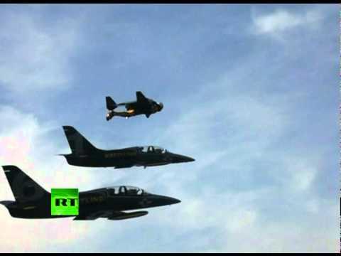 Man flying with jet pack alongside fighter jets