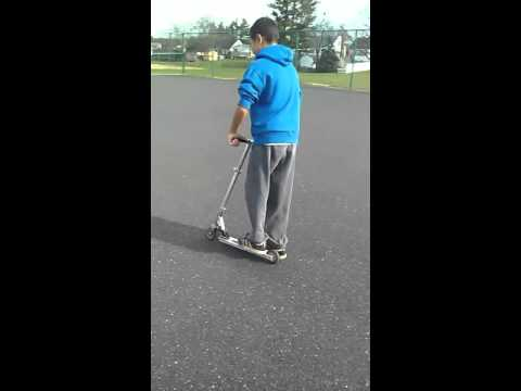 Riding scooter at taney town skate park
