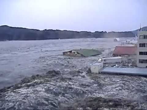 japan earthquake 2011 - Japan tsunami ravaging the city of Kesennuma, in the northeastern part of the country. a wall of water breaches the coastline and starts sweeping away a park...