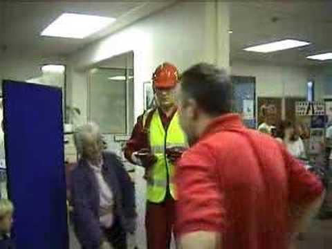 mannequin-man performming as a Living Mannequin: Fall arrest harness being put onto mannequin man by member of the public at a Safety clothing and PPE exhibition by ARCO at family open day at BAE (British Aerospace Engineering) systems in Rochester #2 (flash) for Arco on 06/07/2002