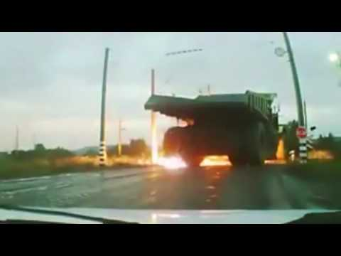 Large Dump Truck drives into high voltage power line, and tires explode.