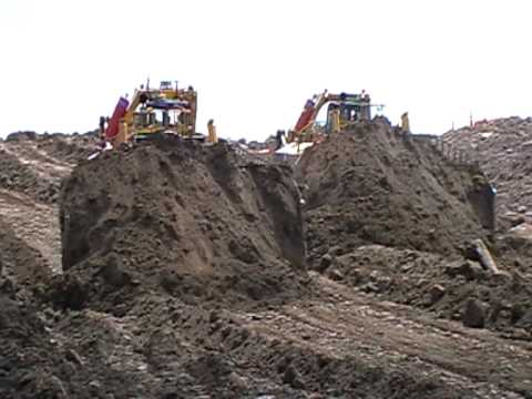 komatsu - Check other videos out!!! two komatsu 575 Dozers pushing a 30 metre wide road in, 160 tonne of material per tractor each pass at stockton mine in new zealand.