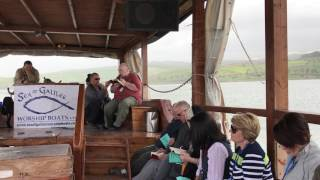 Father Frank reading the Gospel on the Sea of Galilee