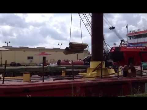 hardwood crane mats being hoisted onto a barge