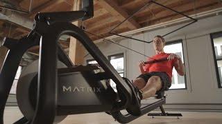 """Wenn schon nicht auf dem Wasser...Der neue Matrix Rower verfügt über ein im Ruderbereich neuartiges, flüsterleises Widerstandssystem. Durch den Einsatz einer Wirbelstrombremse ist das Trainingsgefühl genau wie bei einem Rudergerät mit Luftwiderstand, jedoch kann ohne das sonore Dröhnen der herkömmlichen Propeller-Bauweise. Durch das verschleißfreie System und die enorm reduzierte Geräuschentwicklung ergeben sich neuartige Einsatzmöglichkeiten für den Matrix Rower. In Group Fitness Kursen, Zirkel-, Crossfit- oder Cage-Trainingseinheiten kann eine Vielzahl von Rudergeräten in einem Raum stehen auf denen zum Takt der Musik gerudert wird, ohne dass ein """"akustischer Orkan"""" durch den Kursraum fegt. Nach dem Kurs lässt er sich zudem ganz einfach und platzsparend senkrecht verstauen."""