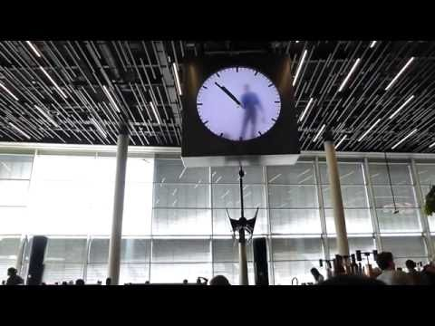 This clock at Amsterdam Schiphol Airport features a video of a man painstakingly painting the time minute by minute.