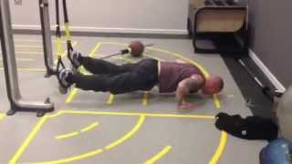 An exercise showing jackknife push ups using the TRX suspension trainer.