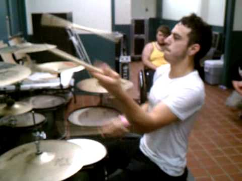 Guy Juggles While Playing Drums.